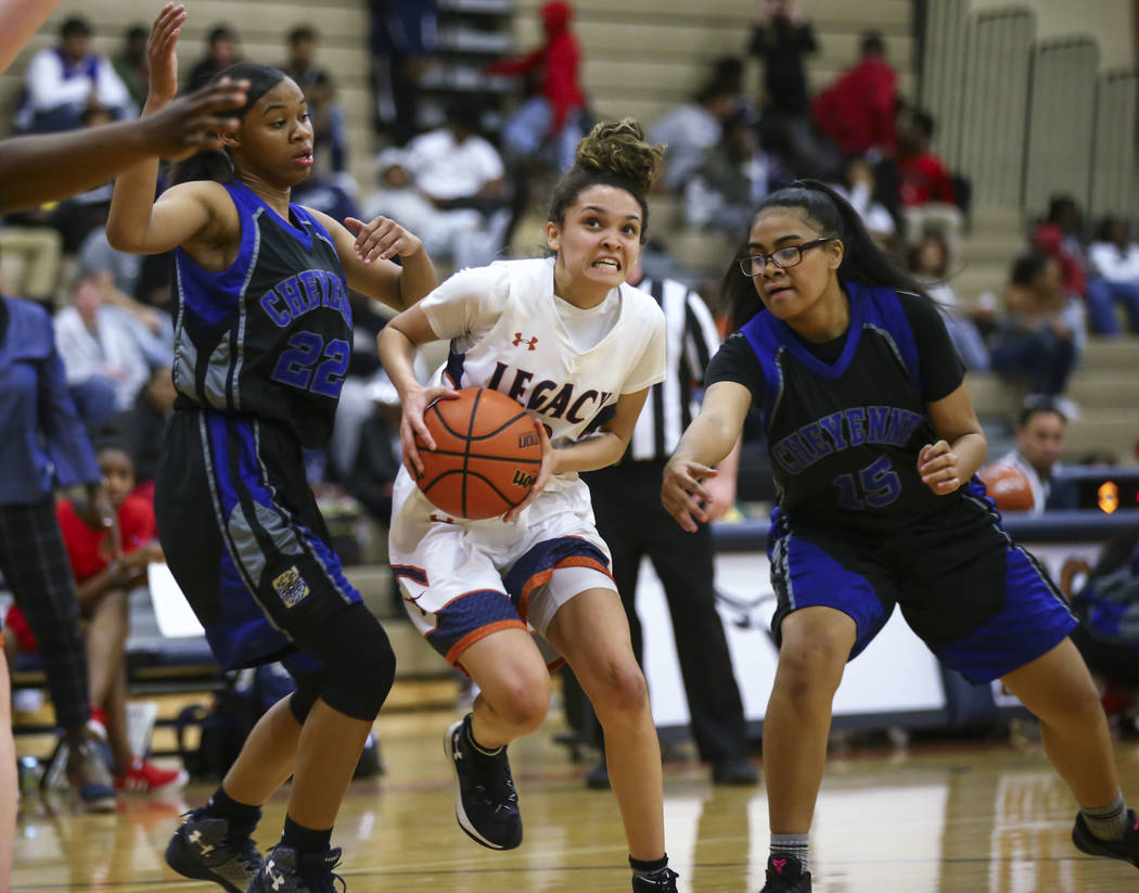 Legacy's Rory Carter (23) drives to the basket against Cheyenne's Brielle Jefferson (15) and Mi'theajah Alexander (22) during a basketball game at Legacy High School in Las Vegas on Thursday, Feb. ...