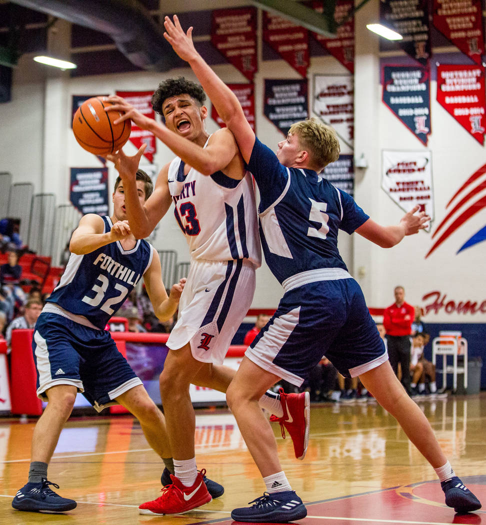 Liberty's Terrance Marigney (13) tries to get around Foothill defenders Dylan Hushaw (32) and Jonah Terrell (5) at Liberty High School in Henderson on Friday, Feb. 2, 2018. Foothill won 69-65.  Pa ...