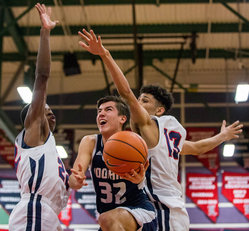 Foothill's Dylan Hushaw (32) looks for a shot while Liberty defenders Jordan Wafer (22) and Terrance Marigney (13) try to block him at Liberty High School in Henderson on Friday, Feb. 2, 2018. Foo ...