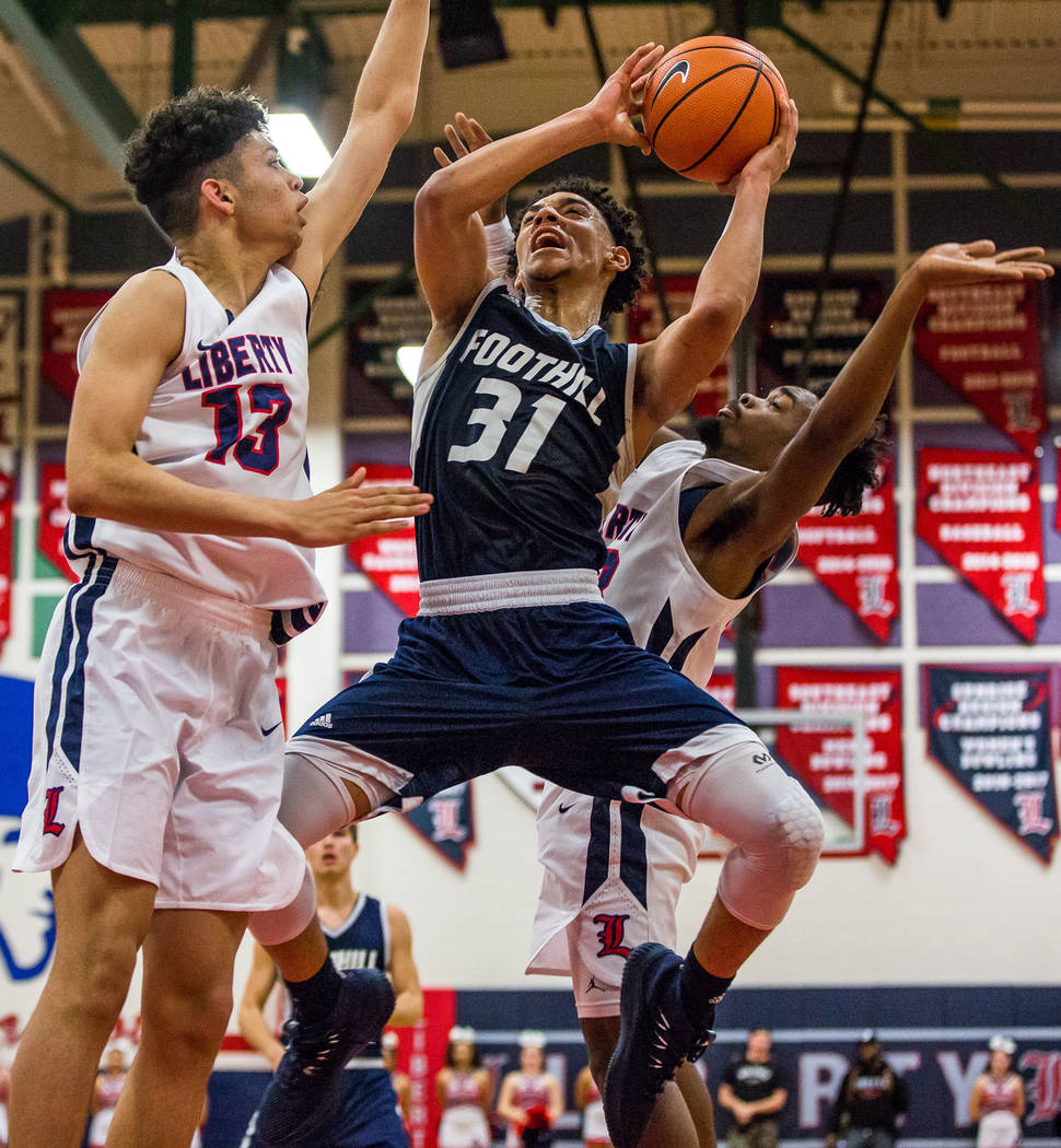 Foothill's Marvin Coleman (31) goes up for a shot while Liberty's Terrance Marigney (13) and Davion Ware (23) attempt to block him at Liberty High School in Henderson Henderson on Friday, Feb. 2,  ...
