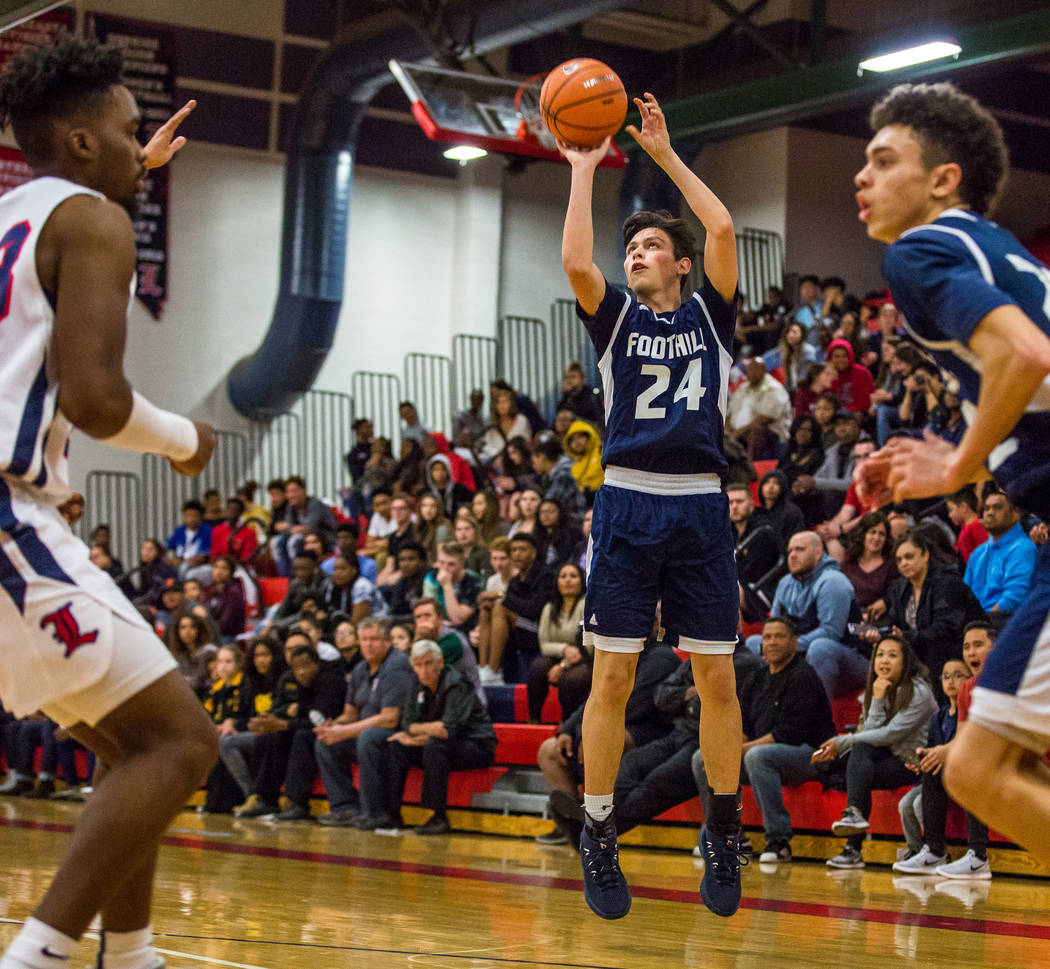 Foothill's Anthony Martin (24) looks for a 3-pointer while Jace Roquemore (22), right, and Liberty's Davion Ware (23), left, watch at Liberty High School in Henderson Henderson on Friday, Feb. 2,  ...