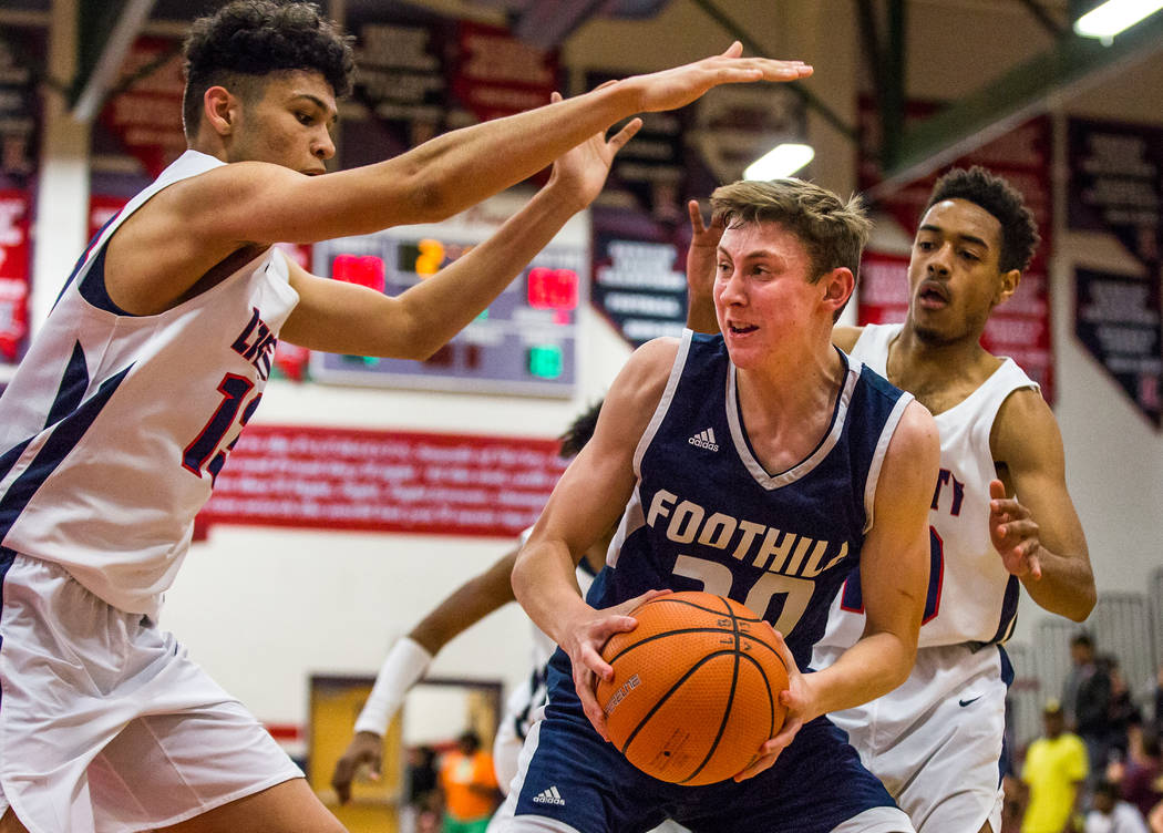 Foothill's Caleb Stearman (20) tries to get the ball away from Liberty defenders Jordan Holt (10), right, and Terrance Marigney (13), left, at Liberty High School in Henderson on Friday, Feb. 2, 2 ...