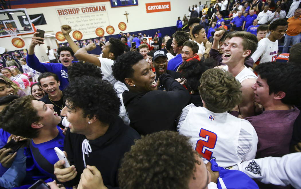 Bishop Gorman's Adrik Lazarou (2) and Noah Taitz, upper right, are surrounded by fans after defeating Clark a basketball game at Bishop Gorman High School in Las Vegas on Friday, Feb. 9, 2018. Cha ...