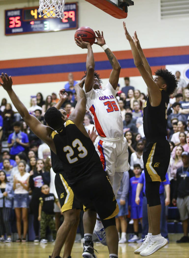 Bishop Gorman's Jamal Bey (35) shoots between Clark's Antwon Jackson (23) and Jalen Hill (21) during a basketball game at Bishop Gorman High School in Las Vegas on Friday, Feb. 9, 2018. Chase Stev ...