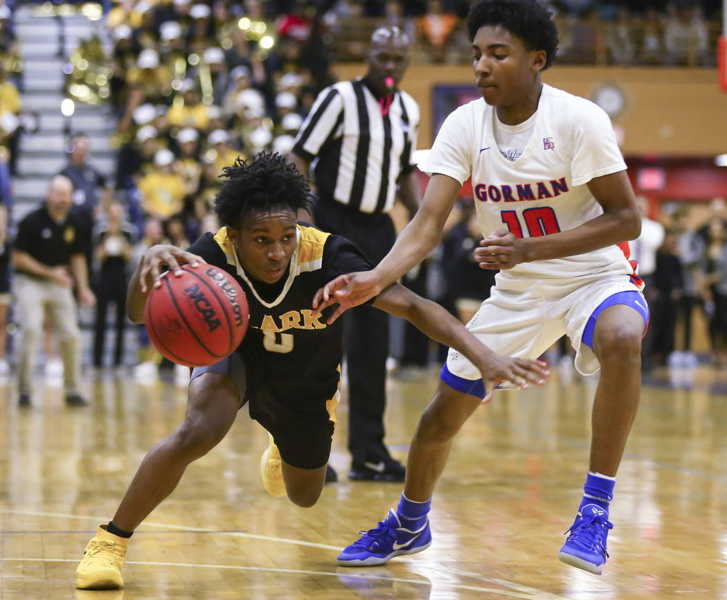 Clark's Joel Burney (0) drives against Bishop Gorman's Zaon Collins (10) during a basketball game at Bishop Gorman High School in Las Vegas on Friday, Feb. 9, 2018. Chase Stevens Las Vegas Review- ...