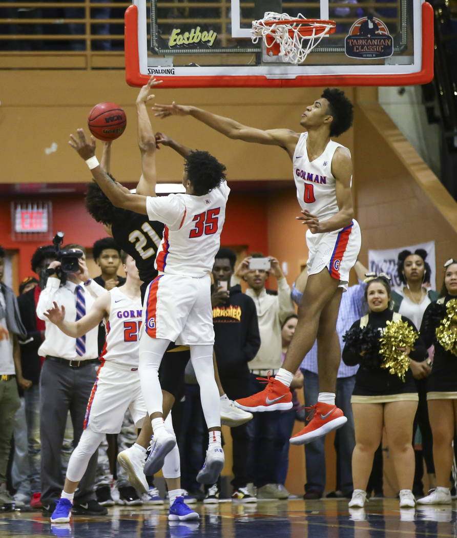 Bishop Gorman's Jamal Bey (35) and Isaiah Cottrell (0) block a shot from Clark's Jalen Hill (21) during a basketball game at Bishop Gorman High School in Las Vegas on Friday, Feb. 9, 2018. Chase S ...