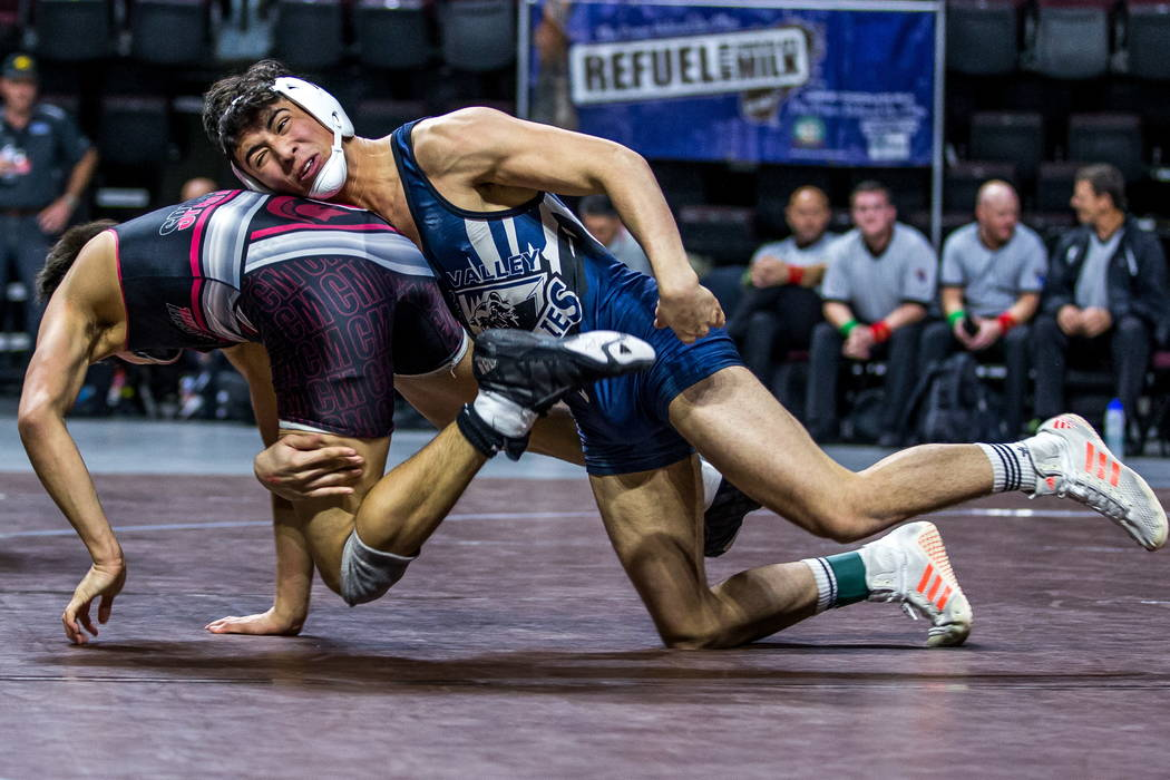 Andres Garcia of Spring Valley, right, tries to pin Nathaniel Rodriguez of Cimarron-Memorial while wrestling in the 4A 132 pounds weight class during the NIAA State Championships at The Orleans in ...