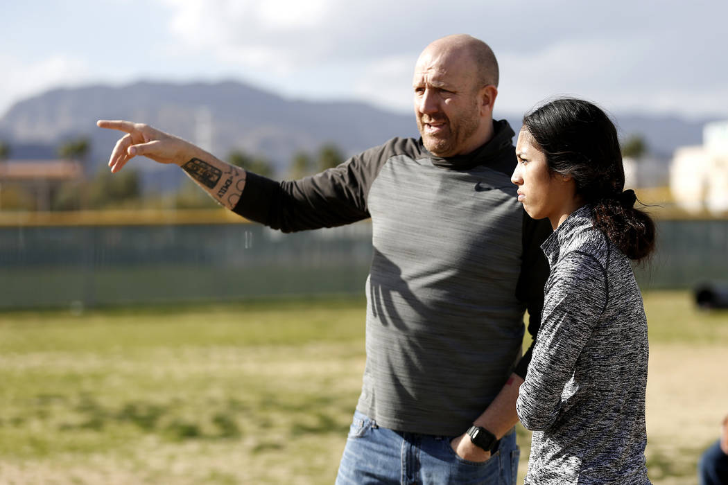 Tiarra Del Rosario, one of the best flag football players in the state, talks to head coach Mark Bailey during practice at Cimarron-Memorial High School in Las Vegas on Monday, Feb. 12, 2018. Andr ...