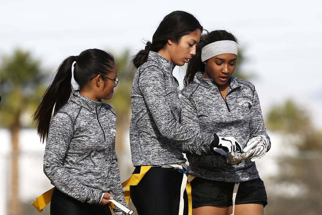 Tiarra Del Rosario, one of the best flag football players in the state, shows Catherine Javan, left, and Mya Bethea, right, the play at Cimarron-Memorial High School in Las Vegas on Monday, Feb. 1 ...