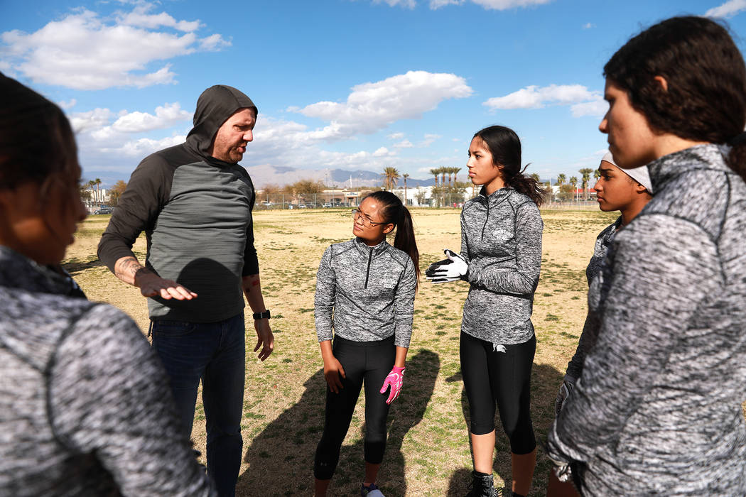 Tiarra Del Rosario, one of the best flag football players in the state, second to right, listens to head coach Mark Bailey during practice at Cimarron-Memorial High School in Las Vegas on Monday,  ...