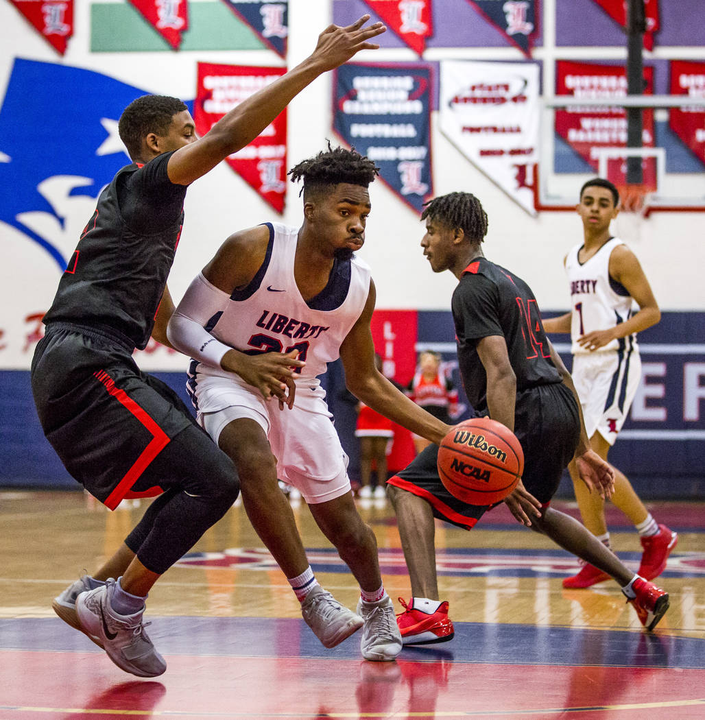 Liberty's Davion Ware (23) attempts to keep the ball away from Las Vegas defenders Zion Edward (22), left, and More Souhamoro (14) at Liberty High School in Henderson on Tuesday, Feb. 13, 2018. Li ...
