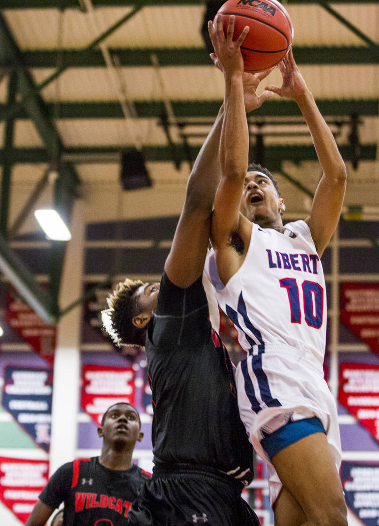 Liberty's Jordan Holt (10) goes up for a shot while Las Vegas' Jaylin Headen (34) tries to grab the ball from him at Liberty High School in Henderson on Tuesday, Feb. 13, 2018. Liberty won 82-70.  ...