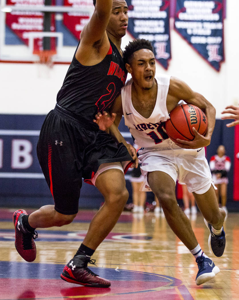 Liberty's Jordan Holt (10) attempts to stiff arm Las Vegas' Zach Matlock (24) out of the way at Liberty High School in Henderson on Tuesday, Feb. 13, 2018. Liberty won 82-70.  Patrick Connolly Las ...