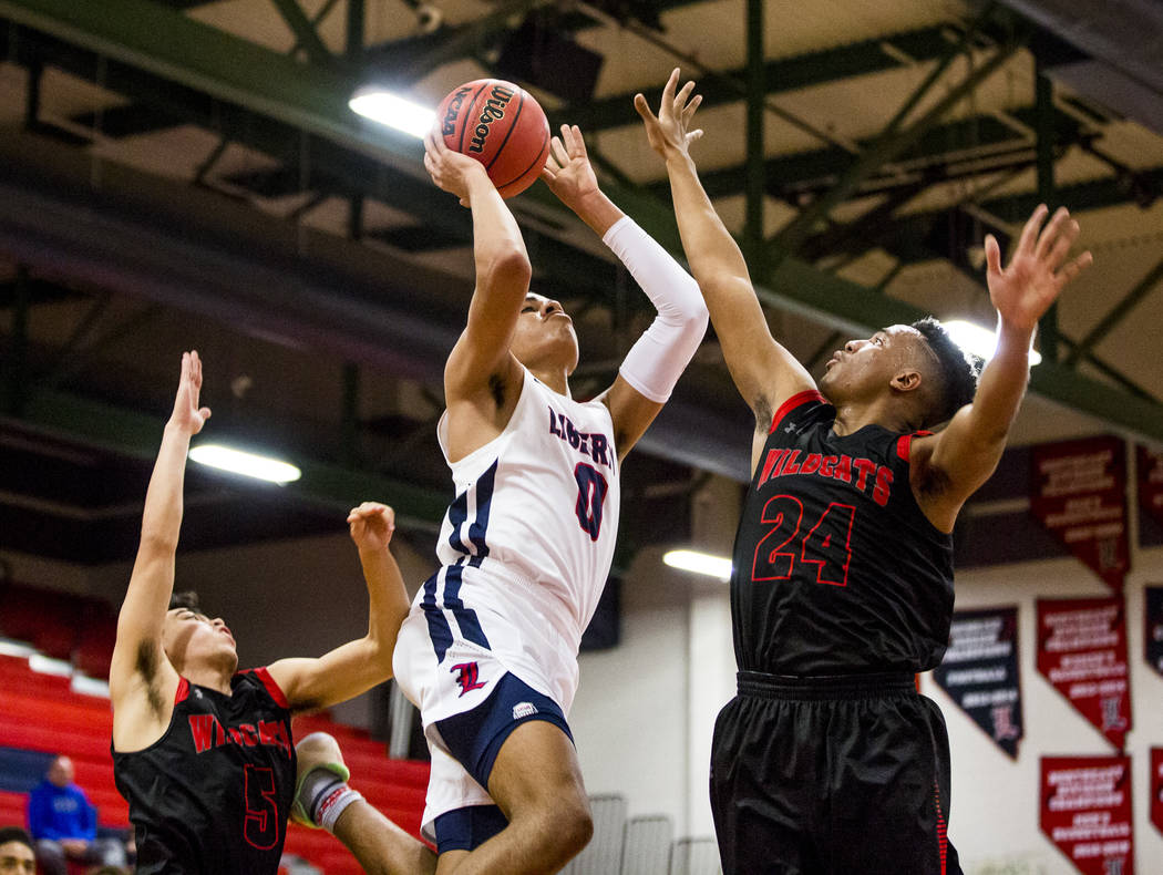 Liberty's Julian Strawther (0) goes up for a shot against Las Vegas defenders Zack Matlock (24) and Adam Pascquali (5) at Liberty High School in Henderson on Tuesday, Feb. 13, 2018. Liberty won 82 ...