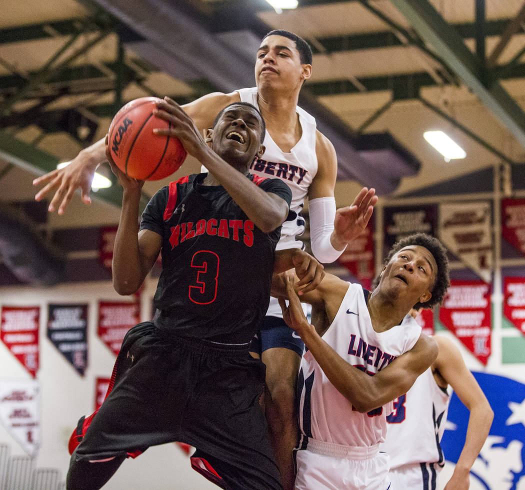 Las Vegas' KJ Johnson (3) goes up for a shot against Liberty defenders Julian Strawther (0), back, and Cameron Burist (15) at Liberty High School in Henderson on Tuesday, Feb. 13, 2018. Liberty wo ...