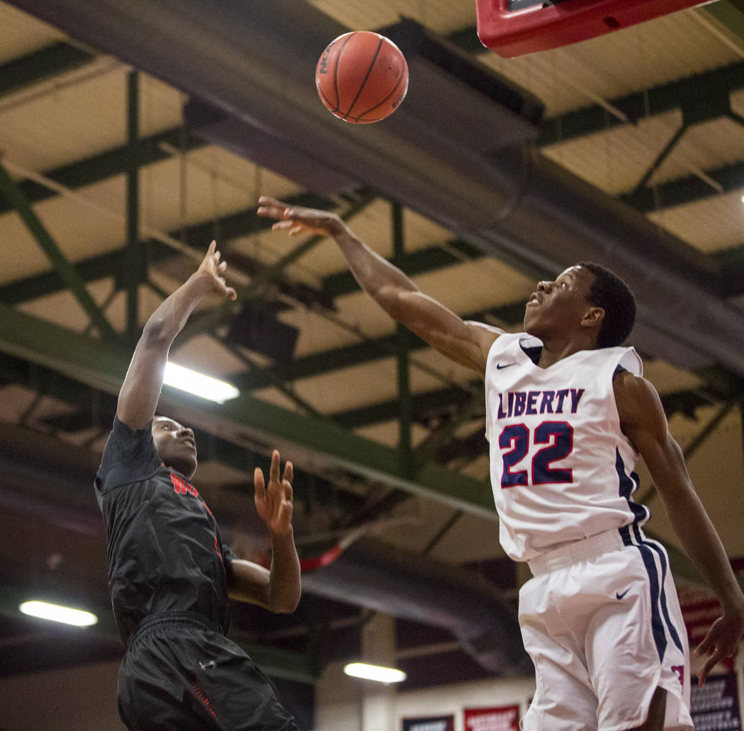 Las Vegas' KJ Johnson (3) throws toward the hoop while Liberty's Jordan Wafer (22) jumps up to block at Liberty High School in Henderson on Tuesday, Feb. 13, 2018. Liberty won 82-70.  Patrick Conn ...