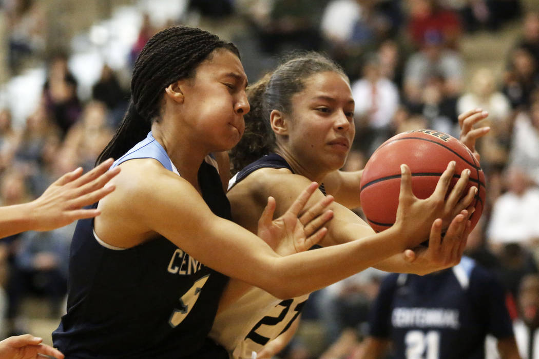 Centennial's Jade Thomas (5) and Spring Valley's Ella Zanders (21) reach for the  ball during the Sunset Region girls basketball championship at Legacy High School in North Las Vegas on Saturday,  ...