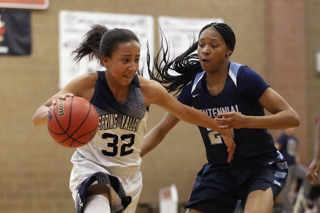 Spring Valley's Garrisen Freeman (32) dribbles around Centennial's Taylor Bigby (20) during the Sunset Region girls basketball championship at Legacy High School in North Las Vegas on Saturday, Fe ...