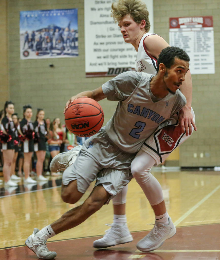 Canyon SpringsՠAlexander Spaight (2), left, dribbles the ball as he is guarded by Desert OasisՠJacob Heese (15), right, during the third quarter of basketball game at Desert Oasis High ...