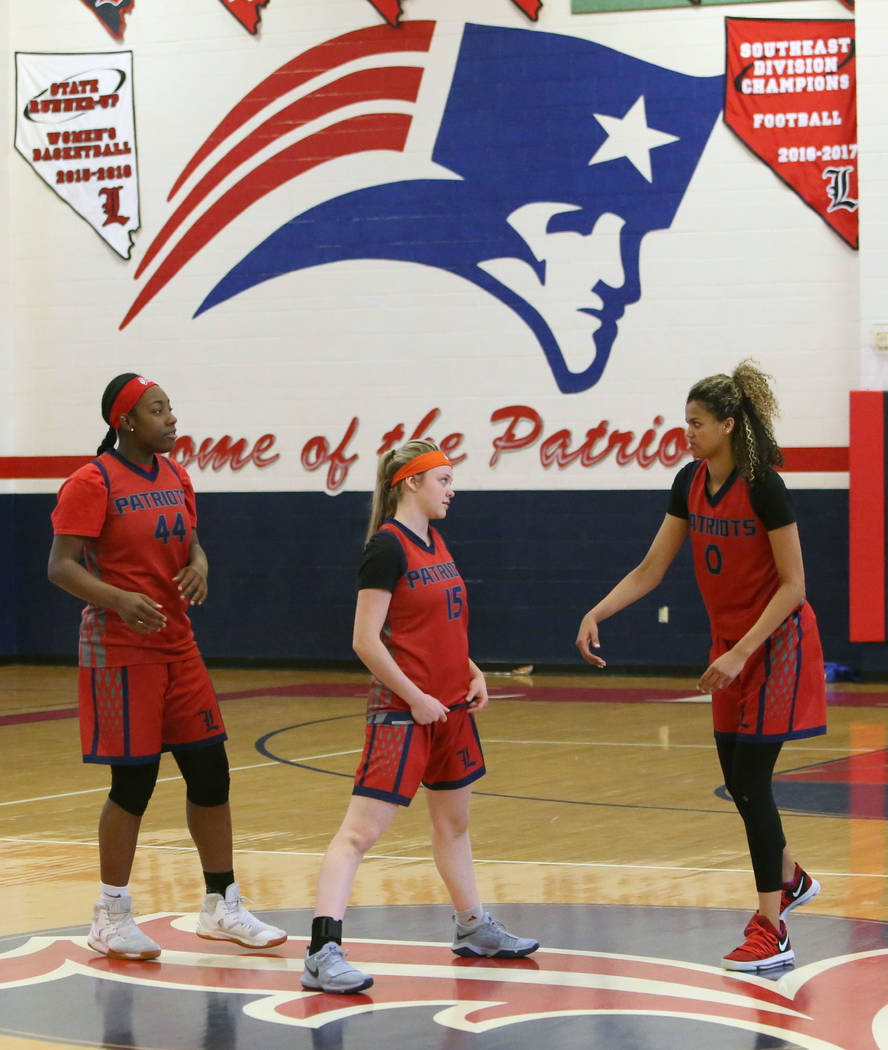 Liberty High's basketball players Dre'una Edwards (44), left, London Pavlica (15) and Rae Burrell (0) stretch during their last day of practice at their school on Tuesday, Feb. 20, 2018, in Las Ve ...