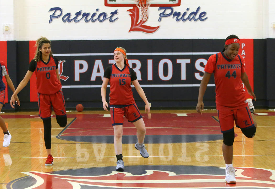 Liberty High's basketball players Rae Burrell (0), London Pavlica (15), and Dre'una Edwards (44) stretch during their last day of practice at their school on Tuesday, Feb. 20, 2018, in Las Vegas.  ...