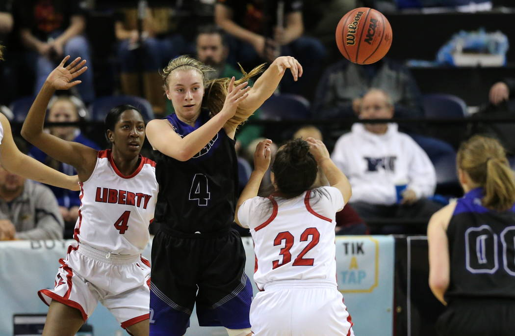 McQueen's Kendra McAninch passes around Liberty defenders Robin Walker, left, and Tedra Tovia during the NIAA state basketball tournament in Reno, Nev. on Thursday, Feb. 22, 2018. Liberty defeated ...