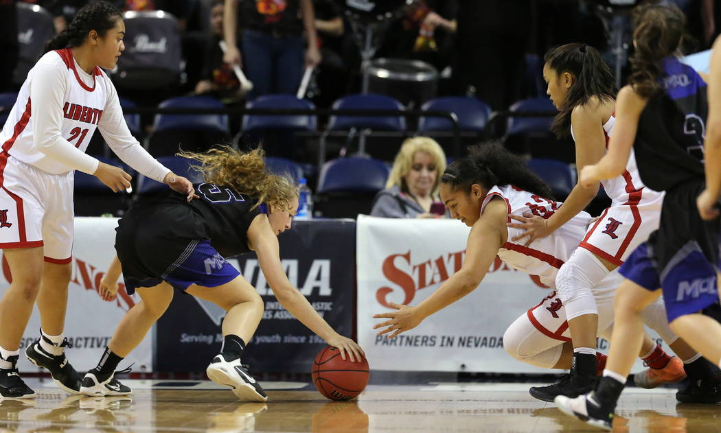 Liberty's Alapese Matauti, right, and McQueen's Mackenzie Corkill reach for a loose ball during the NIAA state basketball tournament in Reno, Nev. on Thursday, Feb. 22, 2018. Liberty defeat ...