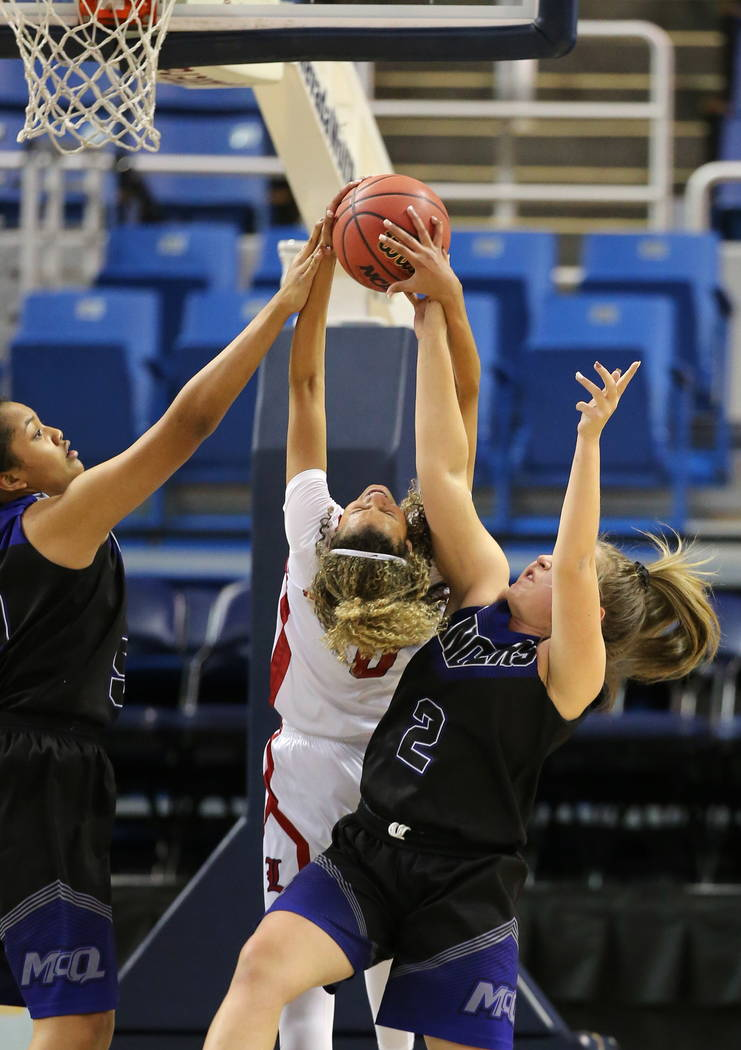 Liberty's Rae Burrell, center,ʠfights for a rebound with  McQueen's Alisi Peaua, left, and Ryan Kindrick during the NIAA state basketball tournament in Reno, Nev. on Thursday, Feb. 22, 2018. ...