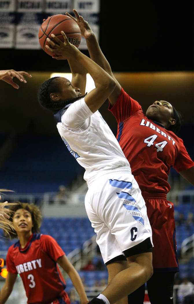 Centennial's Justice Ethridge tries to shoot past Liberty's Dre'una Edwards during the NIAA state basketball tournament in Reno, Nev., on Friday, Feb. 23, 2018. Centennial won the title, 74-65 in  ...