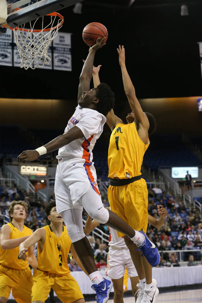 Bishop Gorman's William McClendon shoots past Bishop Manogue defender Joshua Rolling in the 4A NIAA state basketball championship game in Reno, Nev., on Friday, Feb. 23, 2018. Gorman won 62-41. Ca ...