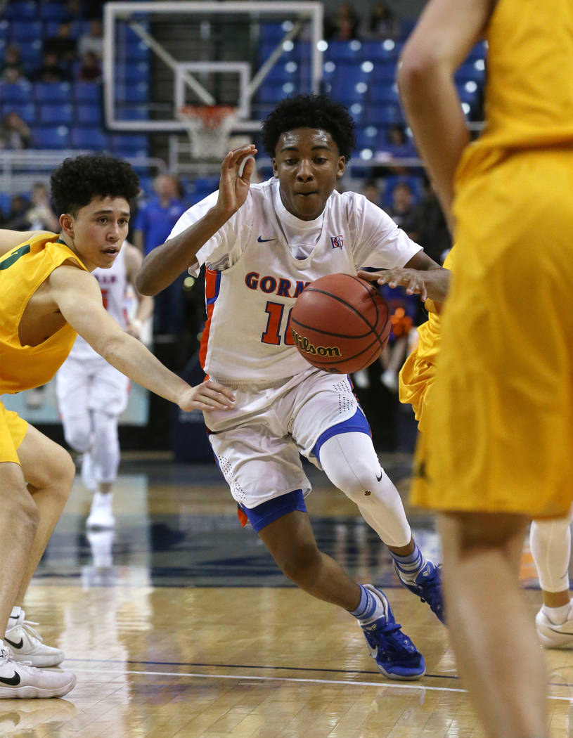 Bishop Gorman's Zaon Collins drives past a Bishop Manogue defender during the 4A NIAA state basketball championship game in Reno, Nev., on Friday, Feb. 23, 2018. Gorman won 62-41. Cathleen Allison ...