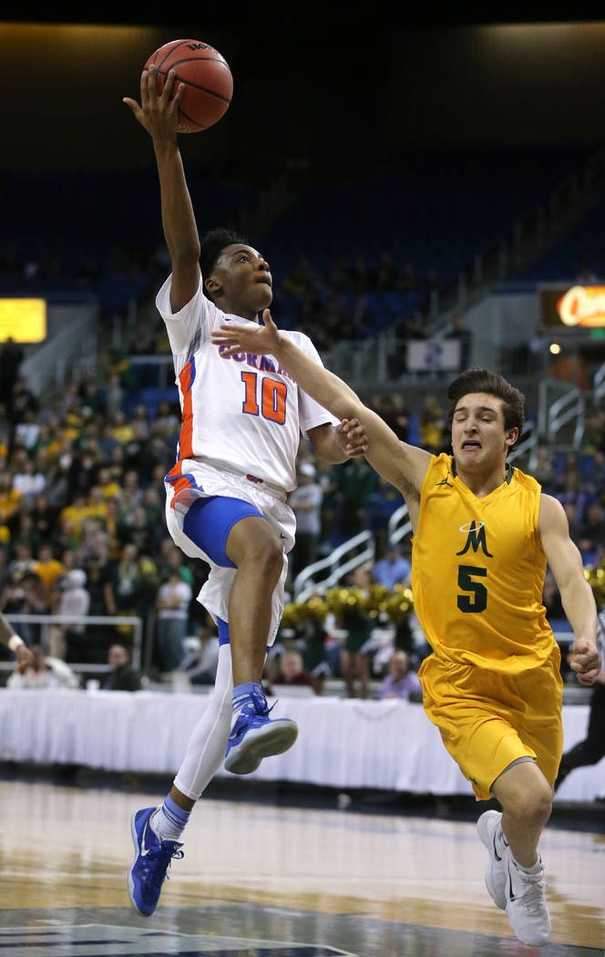 Bishop Gorman's Zaon Collins shoots over  Bishop Manogue defender Mateo Reviglio during the 4A NIAA state basketball championship game in Reno, Nev., on Friday, Feb. 23, 2018. Gorman won 62-41. Ca ...