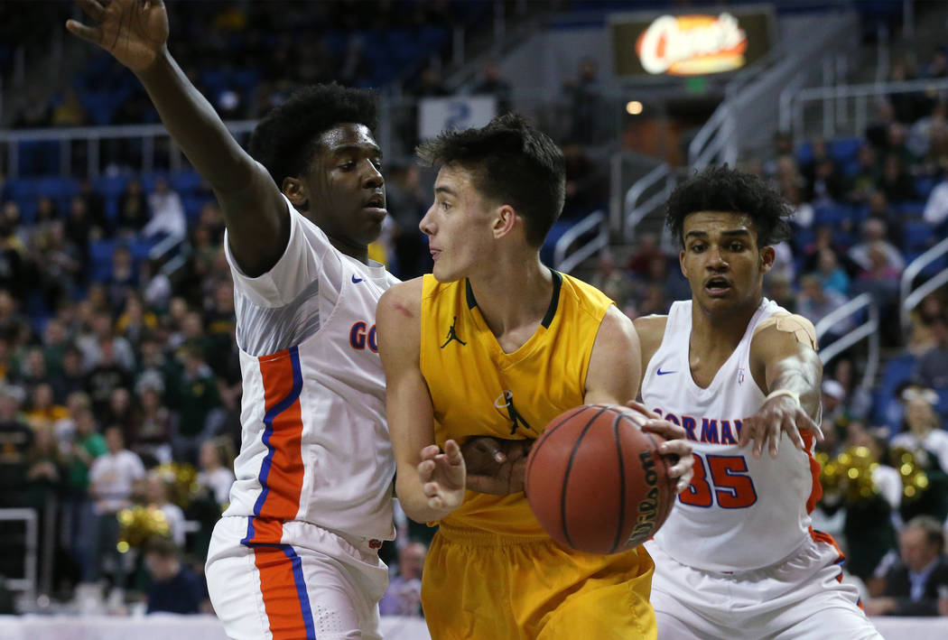 Bishop Gorman defenders William McClendon, left, and Jamal Bey pressure Bishop Manogue's Kolton Frugoli during the 4A NIAA state basketball championship game in Reno, Nev., on Friday, Feb. 23, 201 ...