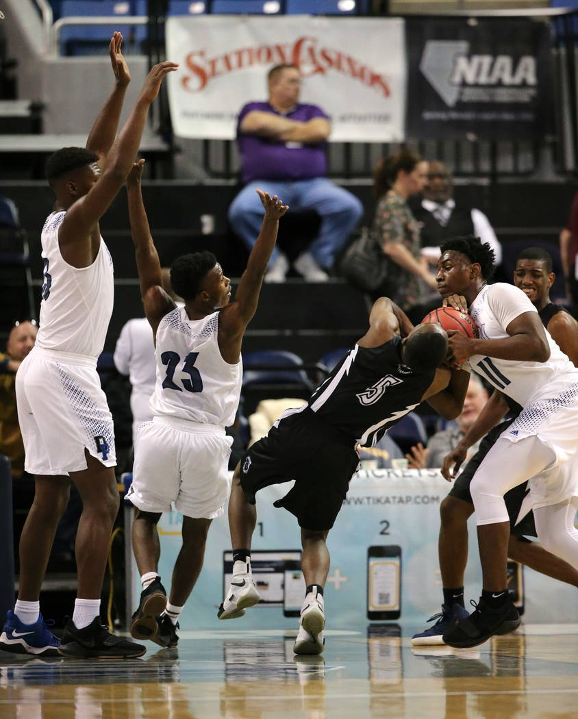 Desert Pines defender Darius Mitchell, right, gets called for a foul in a play with Cheyenne's Kavon Williams during the NIAA 3A state basketball championship game in Reno, Nev., on Saturday, Feb. ...