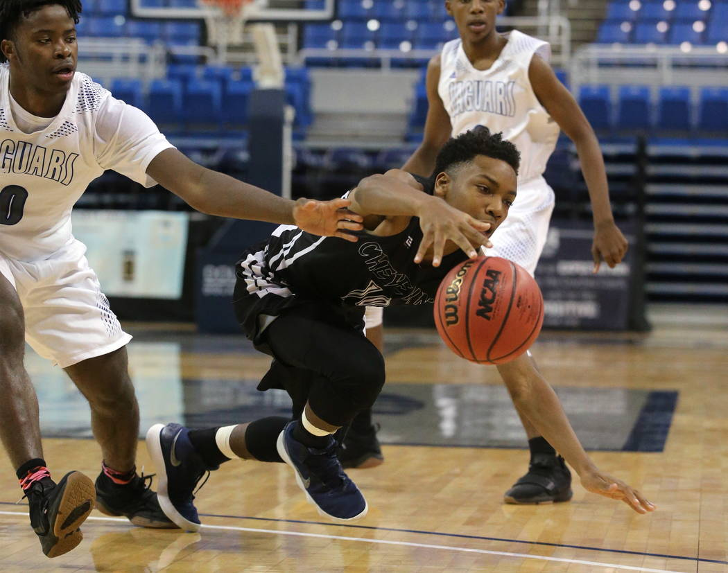 Cheyenne's Jermaine McCormick fights for a loose ball with Desert Pines' Hasani Jameel during the NIAA 3A state basketball championship game in Reno, Nev., on Saturday, Feb. 24, 2018. Desert Pines ...