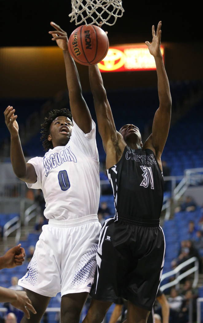 Desert Pines' Hasani Jameel and Cheyenne's Hahsonie Laushaul fight for a loose ball during the NIAA 3A state basketball championship game in Reno, Nev., on Saturday, Feb. 24, 2018. Desert Pines wo ...