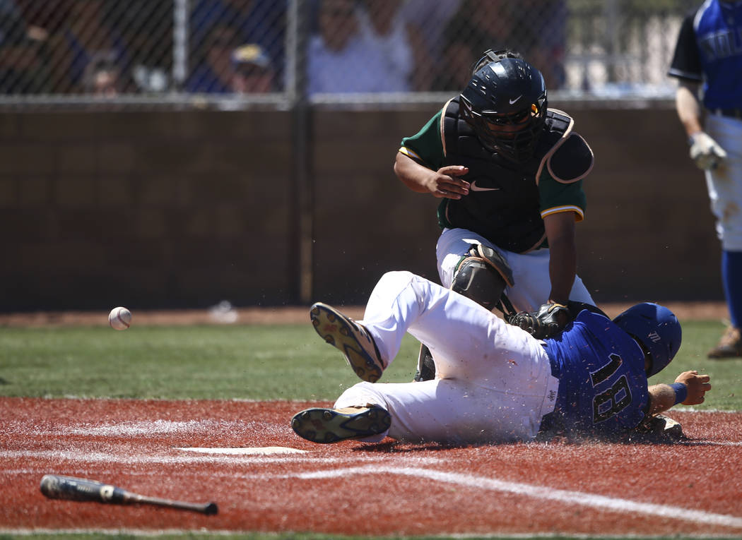 Basic's Trace Evans (18) slides into home base to score a run as Rancho's Miguel Elicerio misses the ball during a Class 4A state baseball tournament game at Las Vegas High School in Las Vegas on  ...