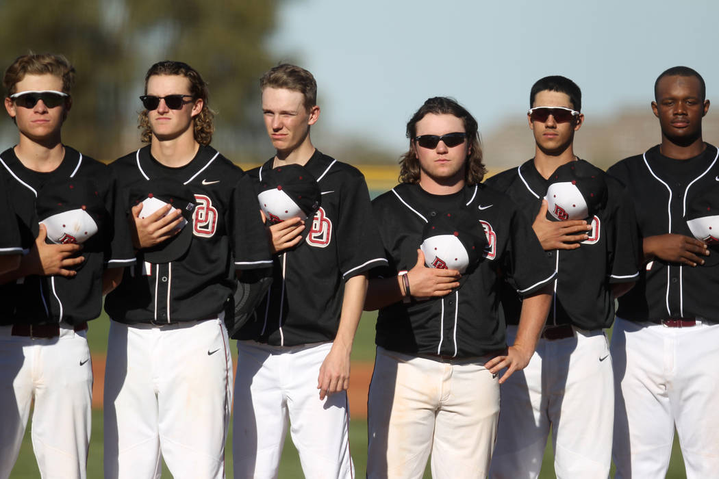Members of the Desert Oasis baseball team stand for the National Anthem prior to the start of their game against Green Valley at Desert Oasis High School in Las Vegas Thursday, March 8, 2018. K.M. ...