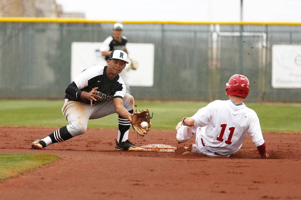 Arbor View Aggies' Tyler Whitaker (11) steals second base before Rancho Rams' Edarian Williams (32) receives a throw at Desert Oasis High School in Las Vegas on Saturday, March 10, 2018. The Rams  ...