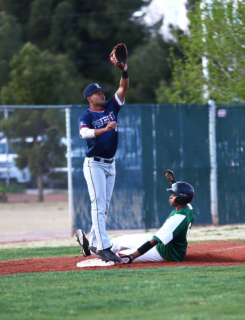 Rancho Rams' Kagen Kennedy (6) slides into third base while Liberty Patriots' Zanden Shim (10) reaches for the throw at Rancho High School on Monday, March 12, 2018, in Las Vegas. The Rams won 11- ...