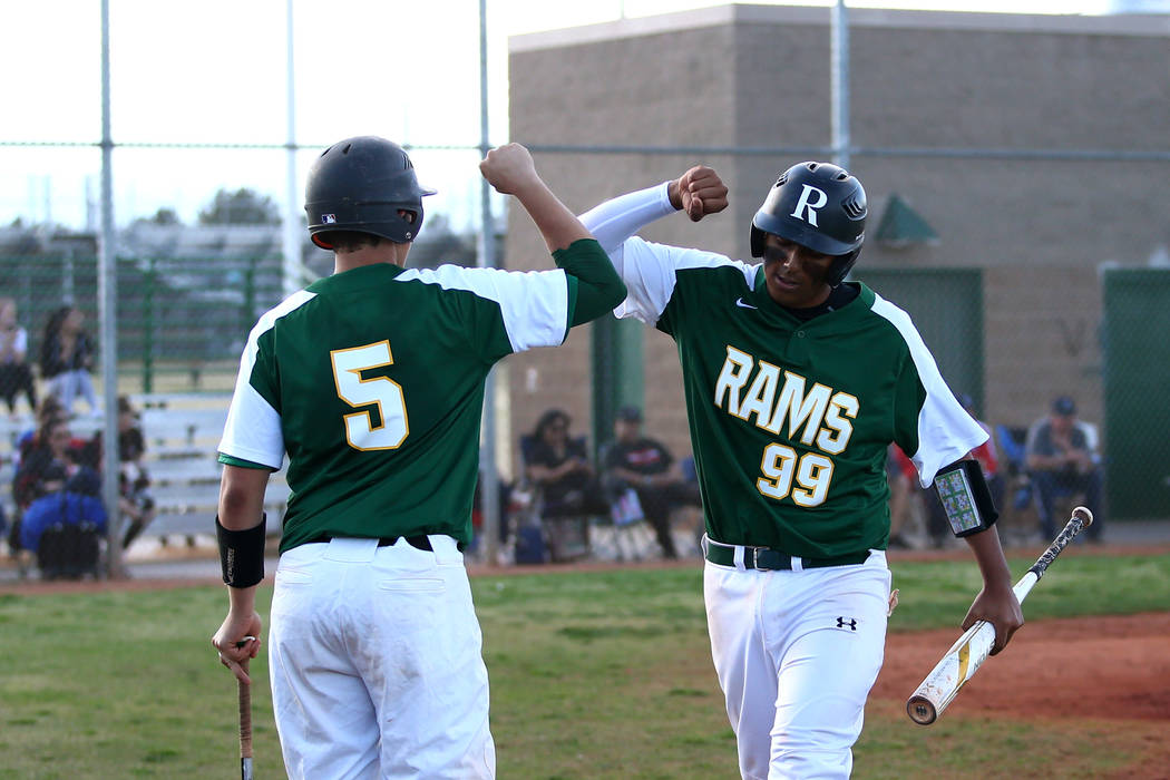 Rancho Rams' Jimmy Gamboa (99) and Matthew Baughn (5) celebrate after a run scored against the Liberty Patriots at Rancho High School on Monday, March 12, 2018, in Las Vegas. The Rams won 11-1. An ...