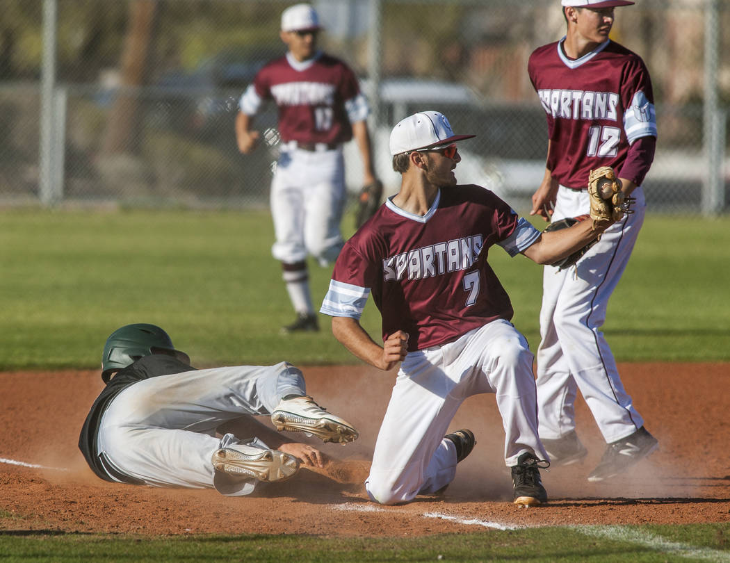 Cimarron-Memorial's Zach Culver (7) and Jack Cannon (12) celebrate after tagging Palo Verde's John Condron out at third at Cimarron-Memorial High School on Wednesday, March 14, 2018. Palo Verde wo ...