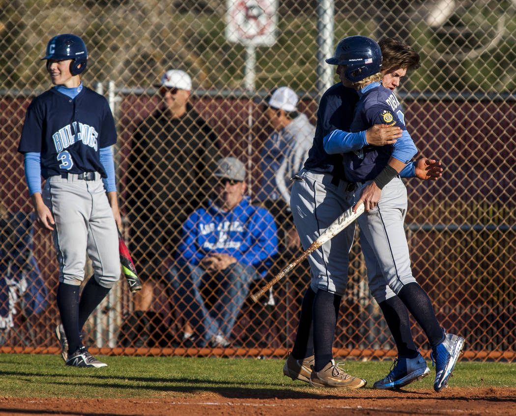 Centennial players Kris Bow and Nik Dobar embrace after Dobar scored the second of two runs in the top of the seventh inning with two outs while playing against Faith Lutheran at Faith Lutheran Hi ...