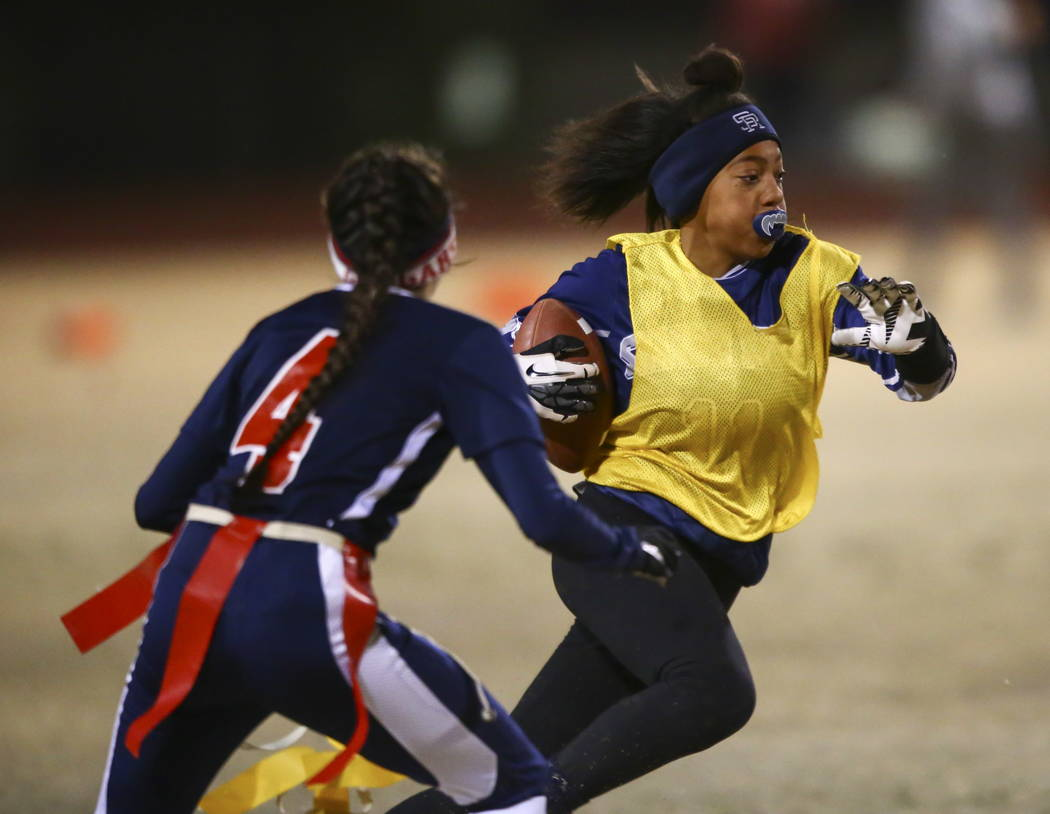 Shadow Ridge's Jordan Ford (11) drives past Coronado's Lexie Potts (4) during the Class 4A state flag football championship game at Cimarron-Memorial High School in Las Vegas on Thursday, Feb. 22, ...