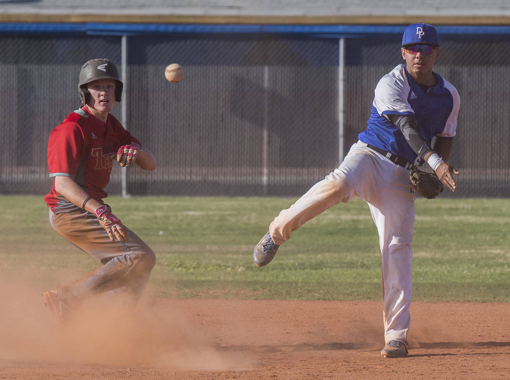 Desert Pines junior shortstop Raymond Minero (6) turns a double play past Southeast Career Tech junior catcher Drew Cole (15) during the Jaguars Class 3A home matchup with the Roadrunners on Tuesd ...