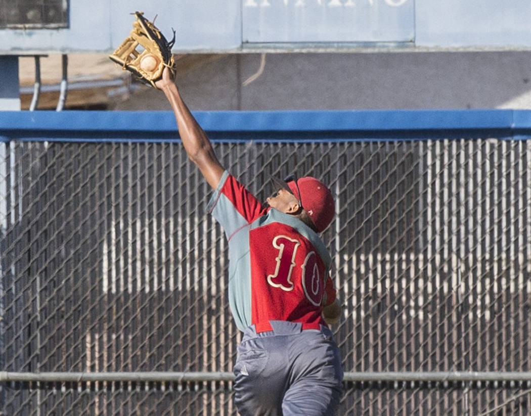 Southeast Career Tech sophomore centerfielder Sean Morgan (10) makes a leaping catch during the Roadrunners road matchup with the Jaguars on Tuesday, April 3, 2018, at Desert Pines High School, in ...