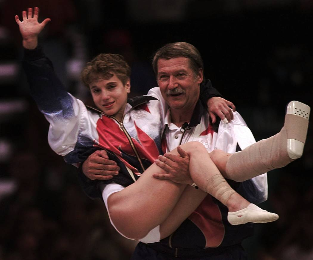 USA's Kerri Strug is carried by her coach, Bela Karolyi, as she waves to the crowd on her way to receiving her gold medal for the women's team gymnastics competition, at the Centennial Summer Olym ...