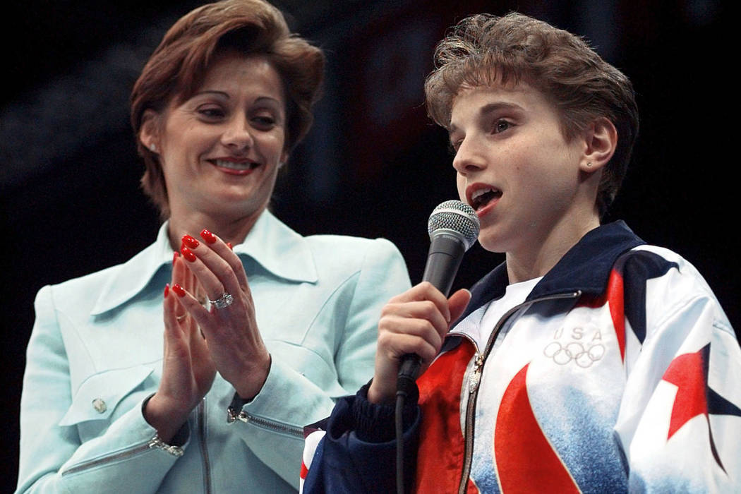 Kerrri Strug, of Houston, Texas, who injured her leg last week in the team competition, addresses the crowd to announce that she will not be competing in the women's individual event gymnastics fi ...