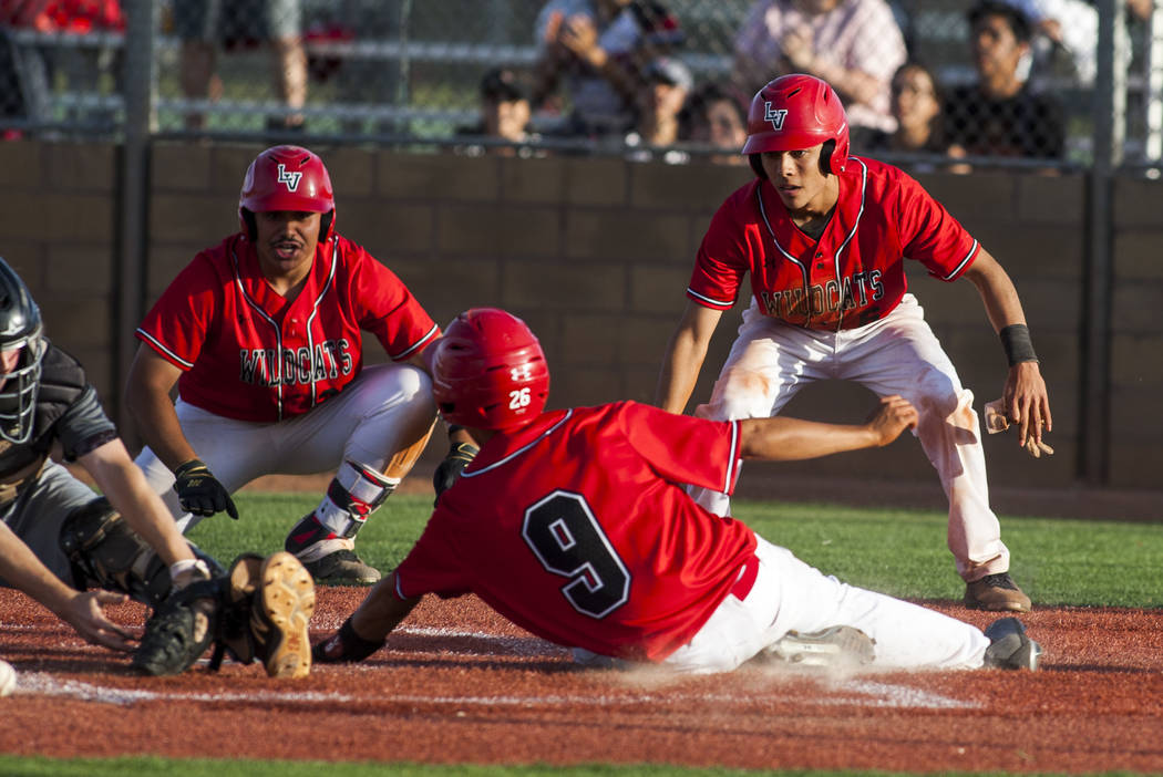 Las Vegas outfielder Jose Martinez slides in safe at home to win the game against Silverado as players Daniel Jimenez, left, and Oliver Haro-Reyes cheer him on at Las Vegas High School on Tuesday, ...