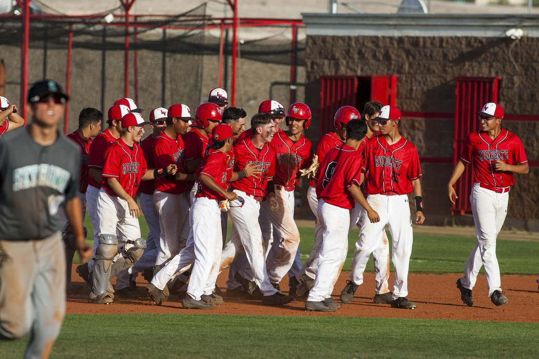 Las Vegas players surround freshman outfielder Joel Lindahl after he scored a two-run single to win the game against Silverado 4-3 in the eighth inning at Las Vegas High School on Tuesday, April 1 ...